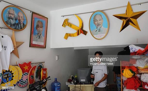 A man stands in his shop selling political decorative items including flags banners communist signs and portraits of Karl MaxLenin and Ho Chi Minh in...