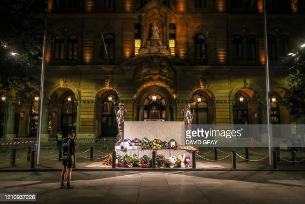 Man stands in respect in front of The Cenotaph monument at Martin Place during the lockdown in Sydney on April 25, 2020. - Australians and New...