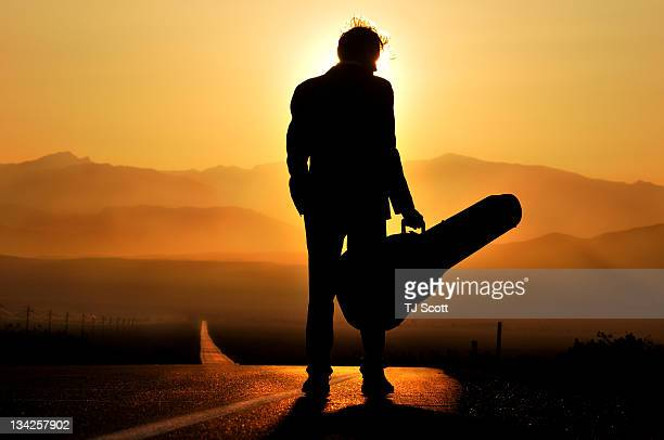 man stands in silhouette with his guitar - guitar case stock pictures, royalty-free photos & images
