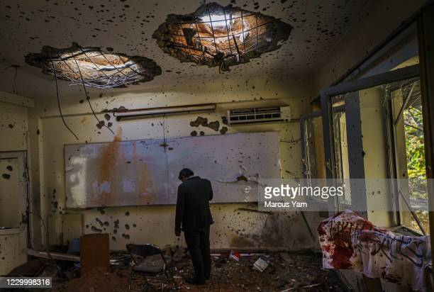 Man stands in the classroom and hangs his head low, in the aftermath of an attack on Kabul University, AfghanistanÕs largest university, where three...