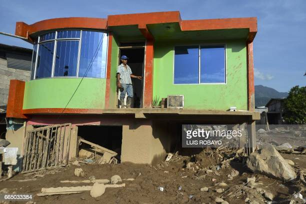 TOPSHOT A man stands in the doorway of his house which was damaged by a mudslide caused by heavy rains in Mocoa Putumayo department Colombia on April...