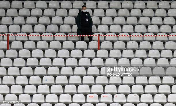 TOPSHOT A man stands in the empty tribune prior to the German first division Bundesliga football match SC Freiburg v Borussia Moenchengladbach on...