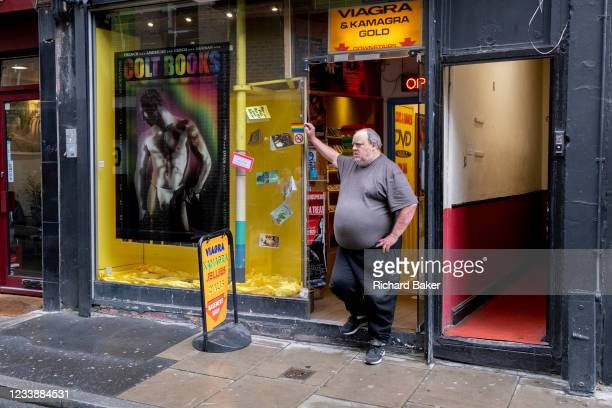 Man stands in the entrance of an Adult Shop whose window features a muscular male in Soho, on 8th July 2021, in London, England.
