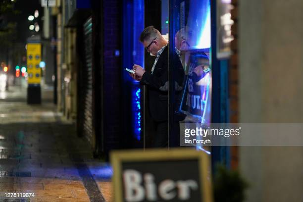 A man stands in the entrance to a pub and checks his phone on October 02 2020 in Middlesbrough England The mayor of Middlesbrough Andy Preston is...