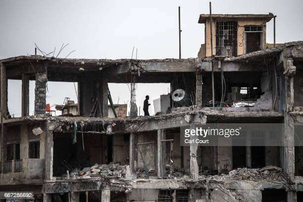A man stands in the ruins of a building destroyed during fighting between Iraqi forces and Islamic State on April 11 2017 in Mosul Iraq Large swathes...