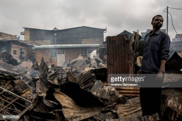 A man stands in the ruins of Kikuyu homes and shops which were destroyed in the Kawangware slum on October 28 2017 in Nairobi Kenya Protests turned...