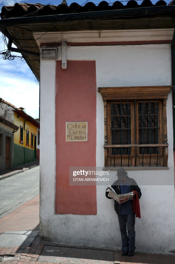 A man stands in the shade as he reads a newspaper in the historic neighborhood of La Candelaria in Bogota on September 17, 2009. La Candelaria is Bogota's oldest neighbourhood and the city's historical center, known for its colonial houses with wooden balconies and clay shingle roofs. AFP PHOTO/Eitan Abramovich /
