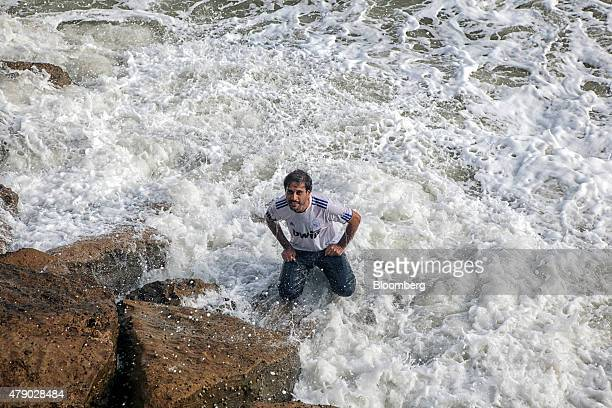 A man stands in the surf at Clifton Beach during a heat wave in Karachi Pakistan on Monday June 29 2015 heat wave where temperatures last week...