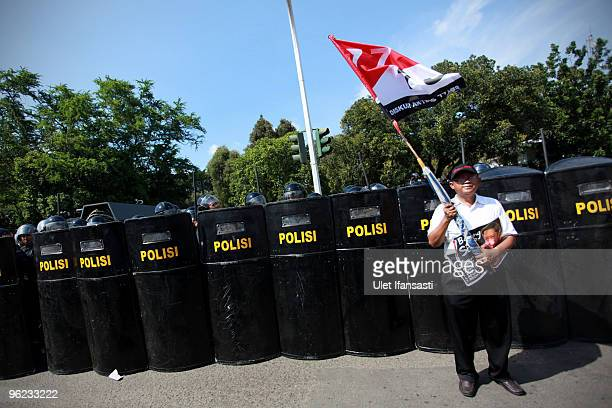 A man stands infront a police line as Indonesians stage a mass antigovernment protest as President Susilo Bambang Yudhoyono marks his 100th day in...