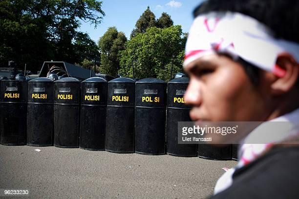 A man stands infront police lines during indonesians stage a mass antigovernment protest as President Susilo Bambang Yudhoyono marks his 100th day in...
