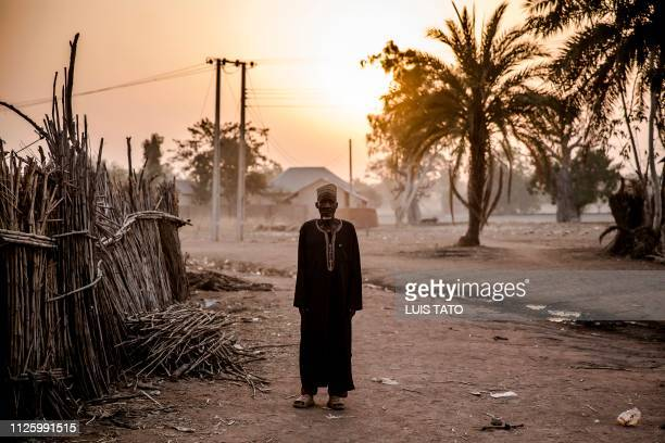 TOPSHOT A man stands inside the Malkohi refugee camp in Jimeta Adamawa State Nigeria on the early morning of February 19 four days ahead of the...