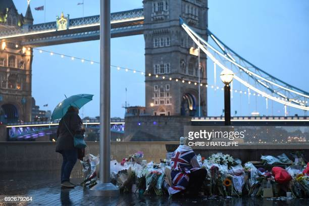 A man stands kneels near flowers layed at Potters Fields Park in London on June 5 after a vigil to commemorate the victims of the terror attack on...