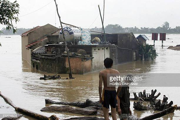 A man stands looking at flooded houses on the banks of the Ma river in the central province of Thanh Hoa 05 October 2007 after Typhoon Lekima hit the...