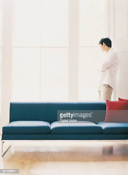 Man Stands Looking Through a Window With his Arms Crossed