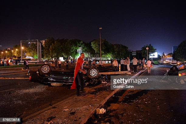 A man stands near a burned car July 16 2016 in Ankara Turkey Istanbul's bridges across the Bosphorus the strait separating the European and Asian...