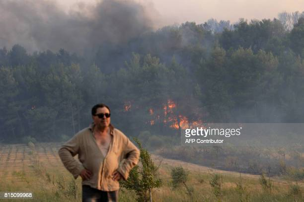 A man stands near a forest fire in Saint Cannat near Aix en Provence in the Bouches du Rhone region More than 350 hectares have burned in the area...