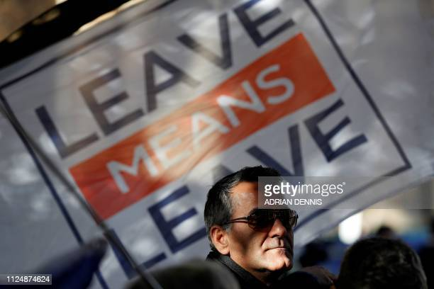 TOPSHOT A man stands near a Leave Means Leave banner as proBrexit activists demonstrate outside of the Houses of Parliament in central London on...
