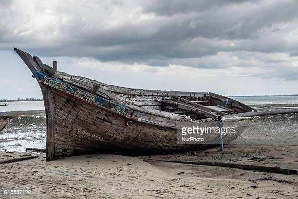 Man stands near an old boat at Mkokotoni village, Zanzibar, Tanzania.