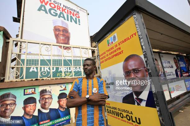 A man stands near campaign posters of Muhammadu Buhari Nigeria's president and candidate of the ruling All Progressives Congress party bottom left...