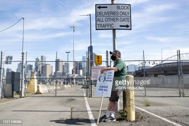 TOPSHOT A man stands near closed Terminal 46 gates during the Juneteenth Shutdown of All Pacific Coast Ports rally and march event organized by...