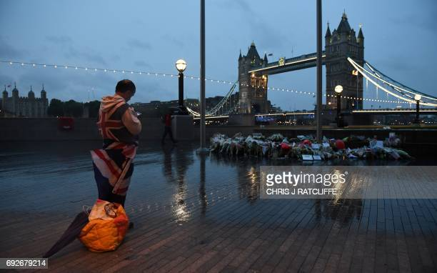 TOPSHOT A man stands near flowers layed at Potters Fields Park in London on June 5 after a vigil to commemorate the victims of the terror attack on...