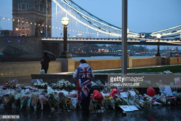 A man stands near flowers layed at Potters Fields Park in London on June 5 after a vigil to commemorate the victims of the terror attack on London...
