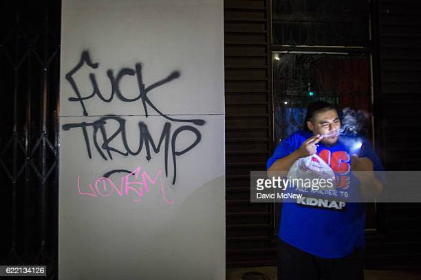 A man stands near freshlypainted antiTrump graffiti as people march to protest the upset election of Republican Donald Trump over Democrat Hillary...