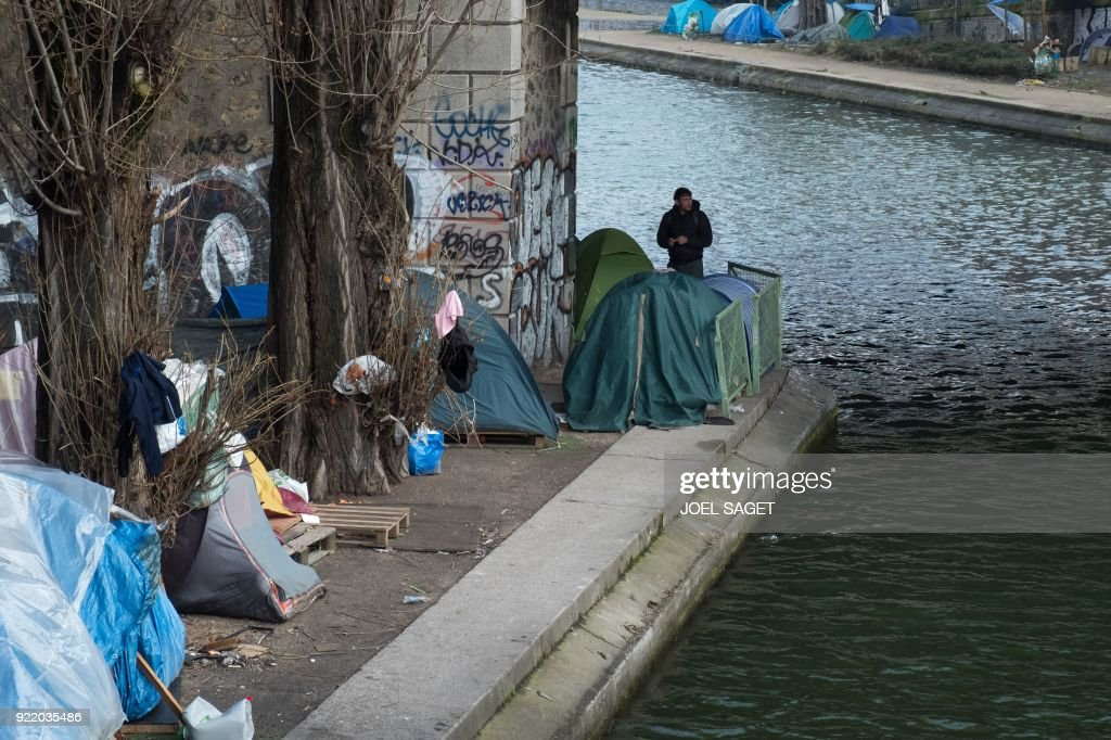 A man stands near tents at a makeshift migrant camp, mainly made up of Afghans, along the Saint-Martin canal in Paris on February 21, 2018. /