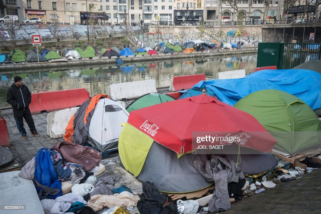 A man stands near tents in a makeshift migrant camp, mainly made up of Afghans, along the Saint-Martin canal in Paris on February 21, 2018. /