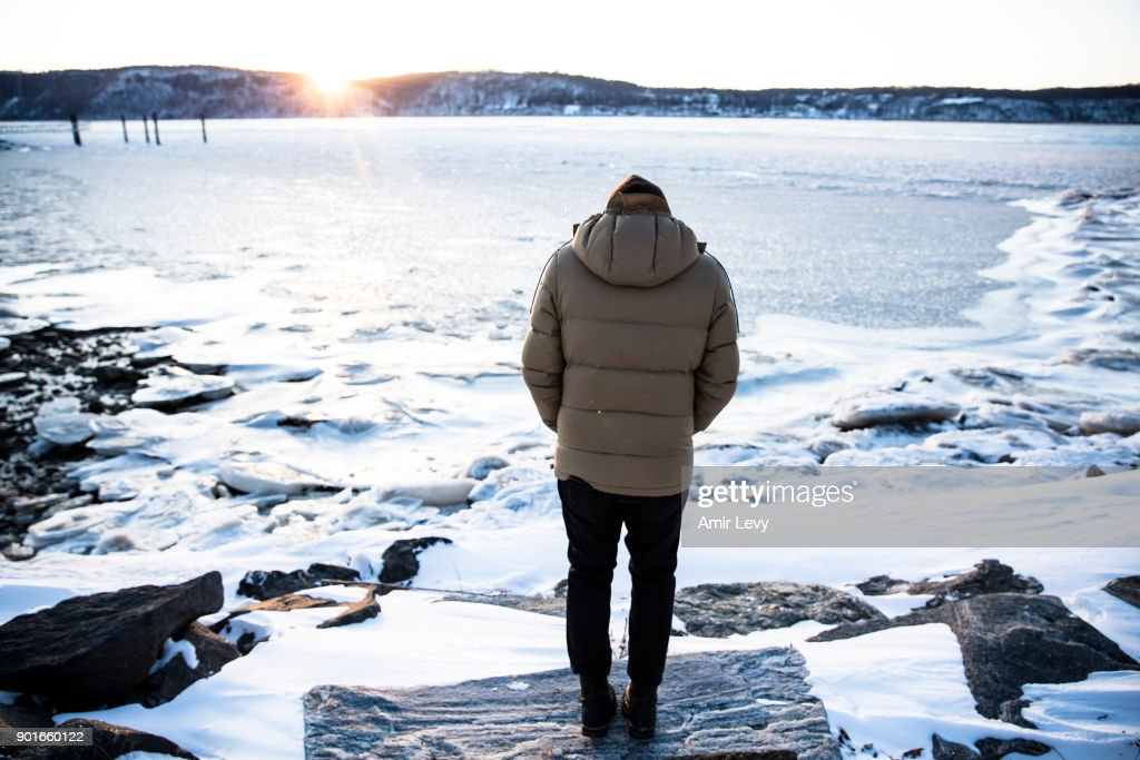 A man stands near the frozen Hudson River on January 5, 2018 in Dobbs Ferry, New York.Extreme low tempratures and wind are expected throghout the weekend in the Northeast.