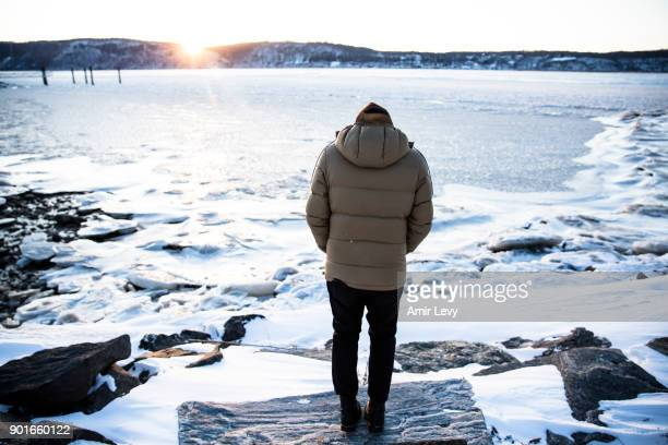 A man stands near the frozen Hudson River on January 5 2018 in Dobbs Ferry New YorkExtreme low tempratures and wind are expected throghout the...