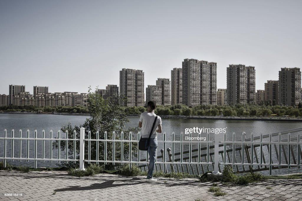 A man stands near the river banks across from new residential buildings in Baotou, Inner Mongolia, China, on Friday, Aug. 11, 2017. China's economy showed further signs of entering a second-half slowdown, as curbs on property, excess borrowing and industrial overcapacity began to bite. Photographer: Qilai Shen/Bloomberg via Getty Images