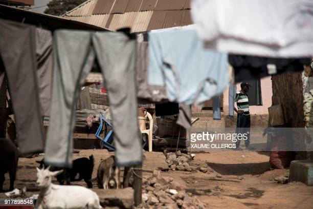 A man stands near wash drying on a line in the Mindara neighbourhood in Bissau on Mardi Gras on February 13 2018 / AFP PHOTO / Xaume Olleros