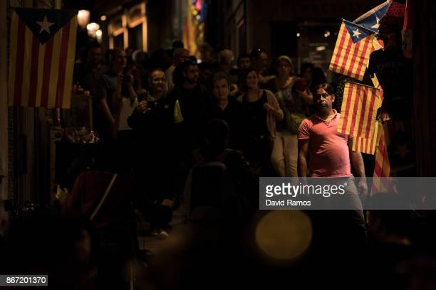 A man stands next Catalan Independence flags known as 'Estelada' on display outside a souvenir shop on October 27 2017 in Barcelona Spain MPs in the...