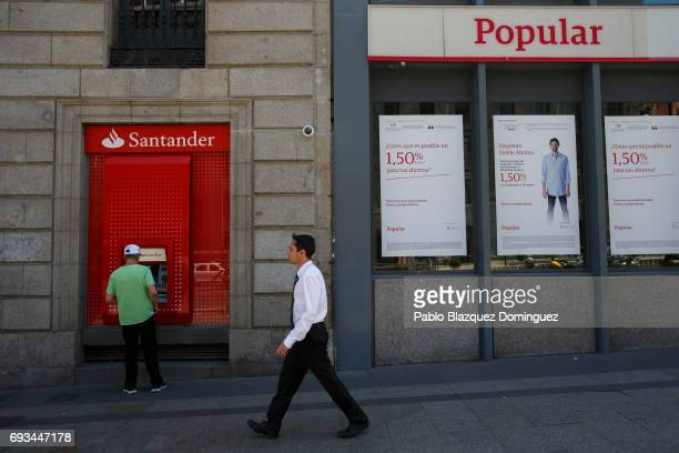A man stands next to a Banco Santander cash machine and a Banco Popular office on June 7 2017 in Madrid Spain Banco Santander SA has announced today...
