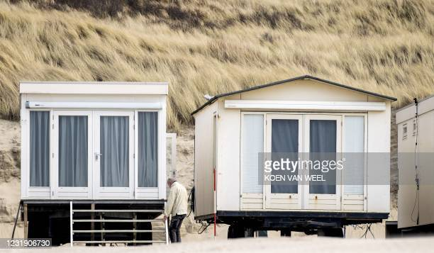 Man stands next to a beach house in Wijk aan Zee, on March 24 2021. - Due to the Covid-19 pandemic, the catering industry is closed, it is only...
