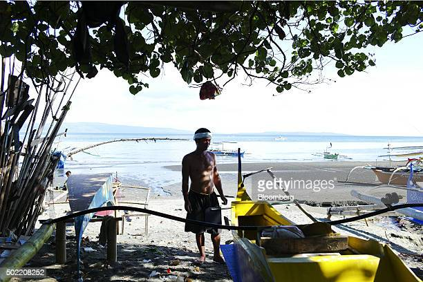 A man stands next to a boat in the Isla Verde shantytown of Davao Mindanao the Philippines on Friday Dec 11 2015 Davao city's reputation as one of...