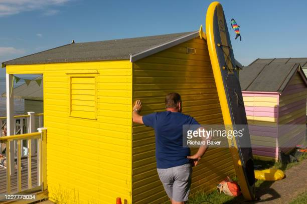 A man stands next to a bright yellow beach hut and waits patiently for his family to come along on the seafront promenade at Whitstable on 18th July...