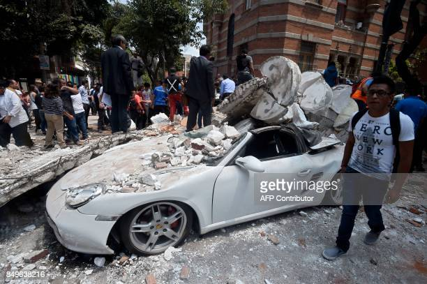 A man stands next to a car crushed by debris from a damaged building after a quake rattled Mexico City on September 19 2017 A powerful earthquake...