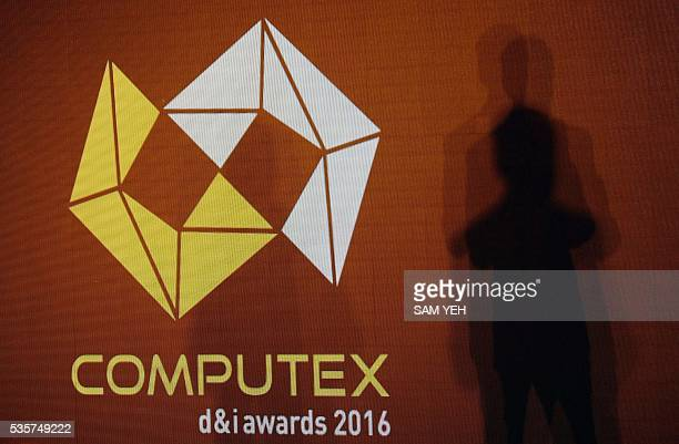 A man stands next to a COMPUTEX logo during a press conference on the eve of the computer expo in Taipei on May 30 2016 More than 5000 booth...