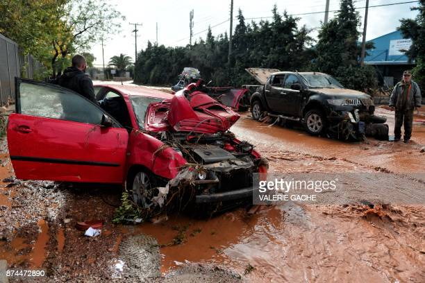 A man stands next to a damaged car stuck in floodwater in the town of Mandra northwest of Athens on November 15 after heavy overnight rainfall in the...