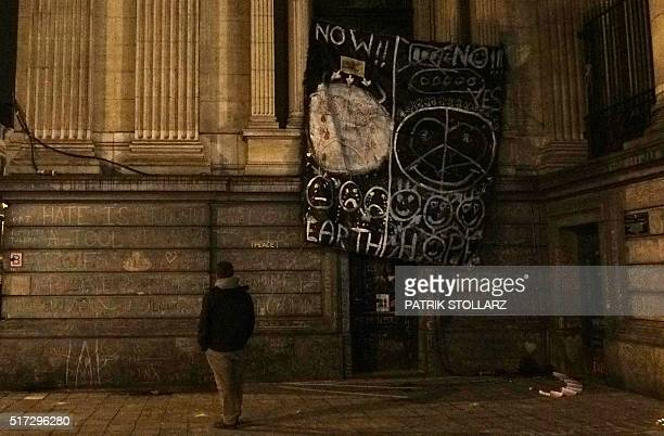 Man stands next to a drawing on March 24, 2016 on place de la Bourse in Brussels, two days after the suicide bombing attacks of terrorists on March...