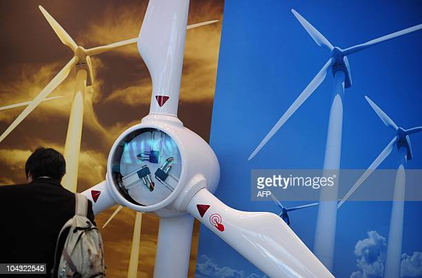 A man stands next to a model of a wind turbine at the Wind Energy 2010 fair on September 21 2010 in Husum northern Germany The fair for Wind Energy...