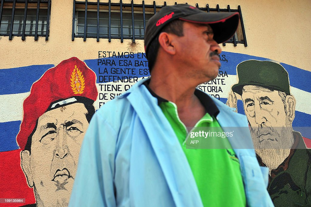 A man stands next to a mural portraying Venezuelan President Hugo Chavez (L) and former Cuban President Fidel Castro in Managua on January 8, 2013. The President of the Venezuelan National Assembly Diosdado Cabello announced today that due to health reasons, Chavez will not be able to take the oath to be sworn in for a fourth term in office next January 10. A constitutional fight intensified with the government planning a massive show of support in the streets on the day he is supposed to be sworn in. Chavez, who underwent his fourth round of cancer surgery in Havana nearly a month ago, is suffering from a severe pulmonary infection that has resulted in a respiratory insufficiency.AFP Photo/Hector RETAMAL