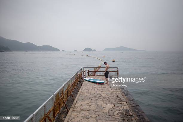 A man stands next to a paddleboard on a jetty in the Repulse Bay area in Hong Kong China on Sunday May 24 2015 Hong Kong developers are poised to...