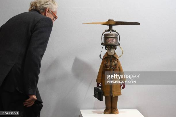 A man stands next to a sculpture entitled 'Représentant Champion à Hélice' by French artist Stephane Halleux during a private preview of the 'START'...