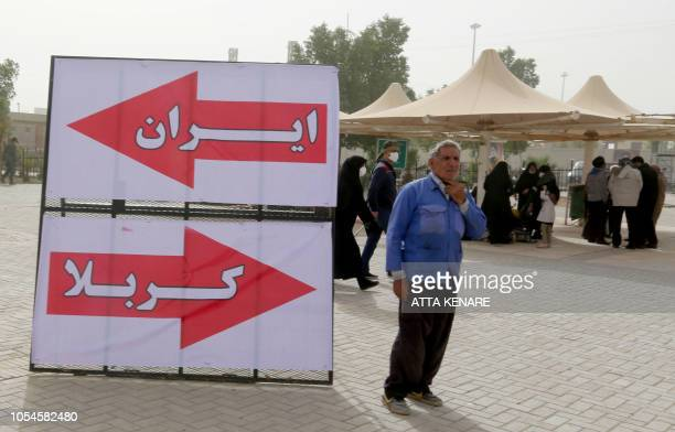 A man stands next to a sign that reads in Farsi and Arabic Iran Karbala at the Mehran border point between Iran and Iraq as thousands of Shiite...