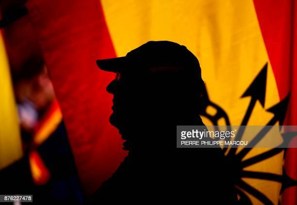 Man stands next to a Spanish flag bearing the yoke and arrows emblem of Francoism during a commemoration marking the 42nd anniversary of the death of...