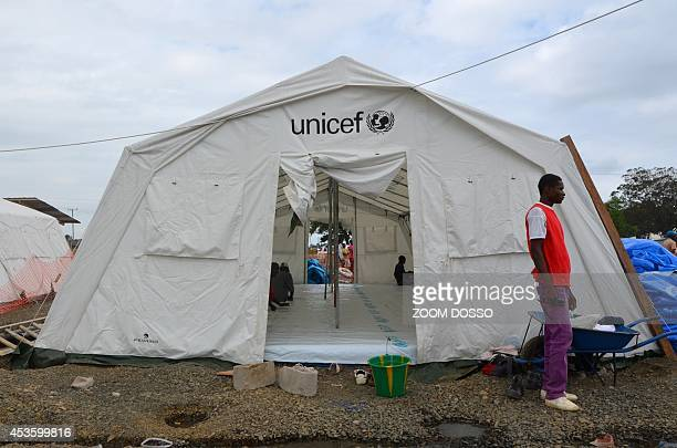 A man stands next to a tent set up to treat Ebola patients on August 12 2014 in Monrovia Liberia one of the hardest hit by the killer virus said it...