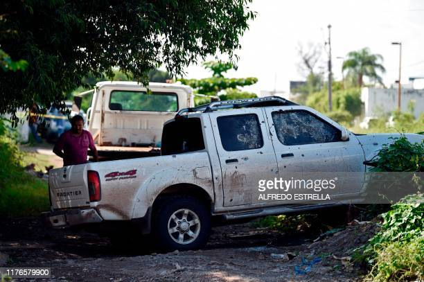 A man stands next to a truck with bullet holes after heavily armed gunmen waged an allout battle against Mexican security forces in Culiacan Sinaloa...